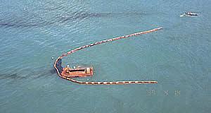 Contenção e remoção com barcaça recolhedora. Notar o arraste do óleo por baixo da barreira devido a ação das correntes marinhas