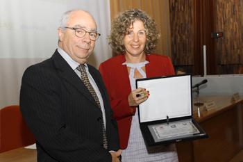 A homenageada Marina Lopes Ribeiro recebe placa do Grupo Ozônio, das mãos do senhor Wadi Tadeu Neaime.